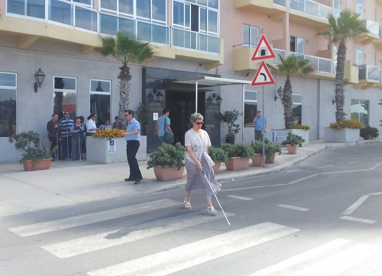 Woman long cane user crossing at a zebra crossing